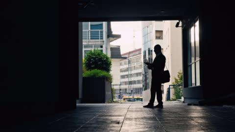 stockvideo's en b-roll-footage met slo mo silhouet van een zenuwachtig kijkende zakenman die in onderdoorgang loopt - werkloosheid