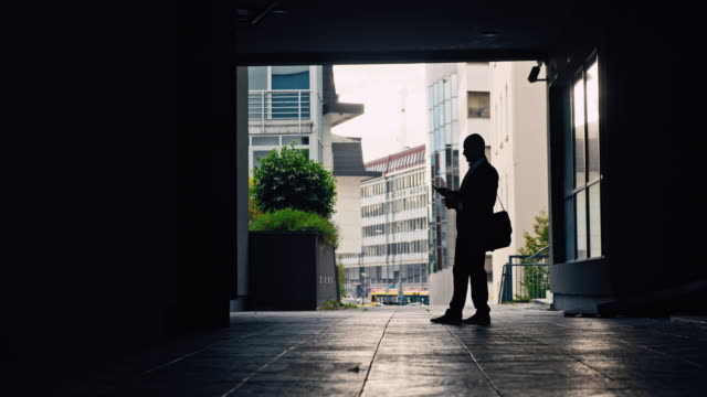 slo mo silhouette of a nervous looking businessman walking in underpass - unemployment stock videos & royalty-free footage