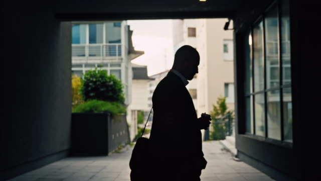 slo mo silhouette of a nervous looking businessman walking in underpass - 1 minute or greater stock videos & royalty-free footage