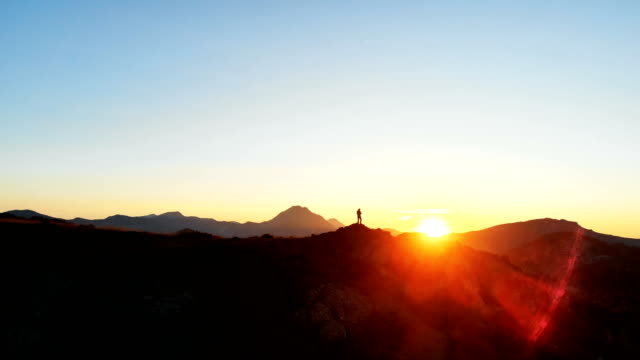 silhouette of a person in the top of a mountain aerial - controluce video stock e b–roll