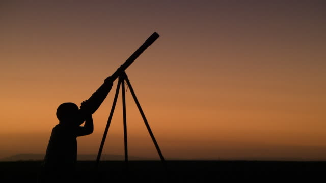 Silhouette of a person looking through a telescope