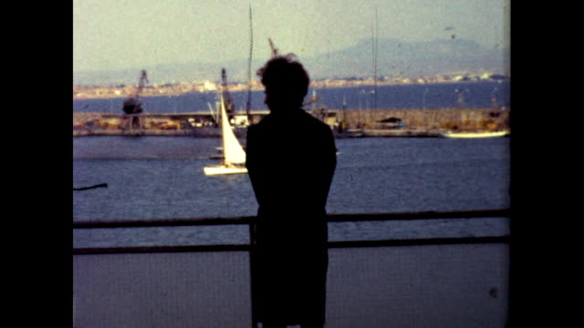 silhouette of a person standing by the pier; various yachts passing by on the water - silhouette stock videos & royalty-free footage