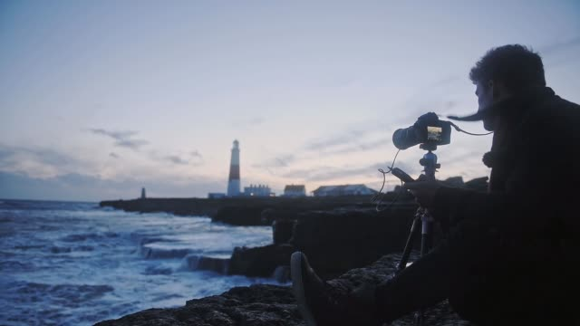 silhouette of a photographer sitting on the shore with his camera on a tripod taking videos of waves splashing in the ocean in dorset, england on a sunset - closeup shot - photographer stock videos & royalty-free footage