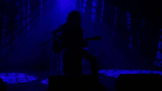 vídeos de stock, filmes e b-roll de ls silhueta de um roqueiro tocando guitarra no palco - cantora