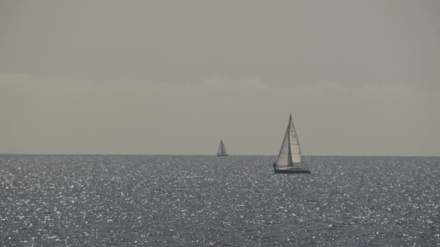 silhouette of a sailing yacht out at sea. - bournemouth england stock videos & royalty-free footage