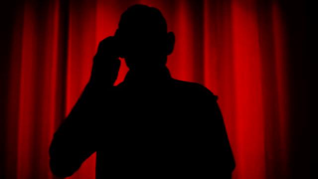 vídeos y material grabado en eventos de stock de silueta de un hombre mayor con smartphone - contraluz