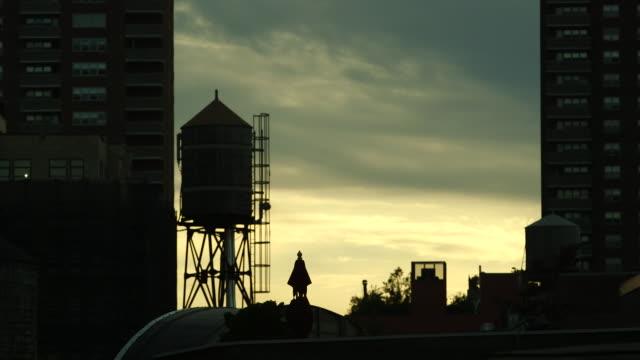 vídeos de stock, filmes e b-roll de silhouette of a small water tower on a manhattan rooftops - tanque de armazenamento