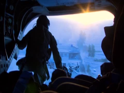 silhouette of a soldier in military aircraft flying over afghanistan at dawn - 2001年~ アフガニスタン紛争点の映像素材/bロール