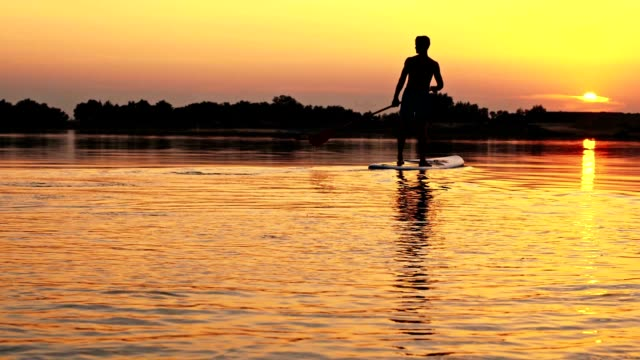 SLO MO silhouet van een stand-up paddleboarder