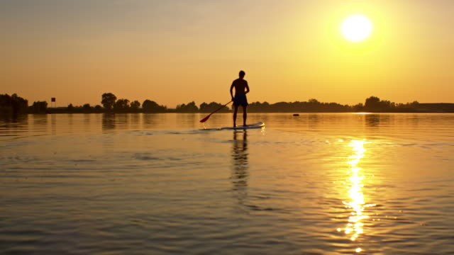 Silhouette of a SUP on the lake at sunset