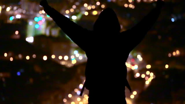 Silhouette of a traveller sightseeing the Barcelona city at night from elevated viewpoint raising arms with the Barcelona cityscape.