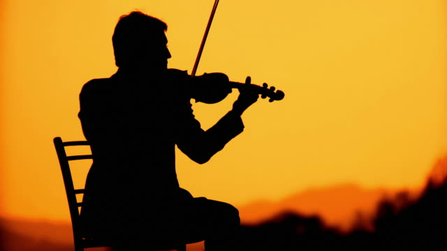 HD: Silhouette Of A Violinist At Sunset