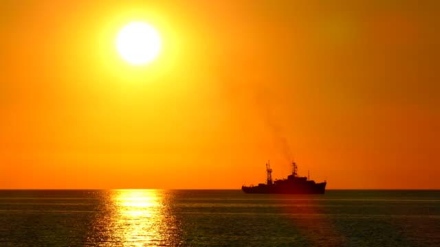 silhouet van een oorlogsschip tegen de achtergrond van de ondergaande zon
