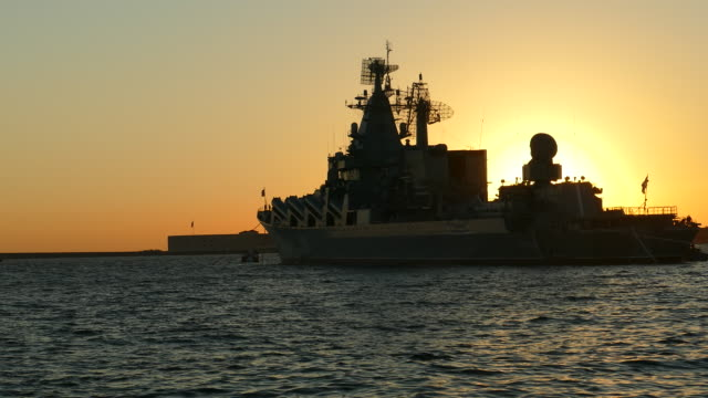 silhouette of a warship and the sun at sunset