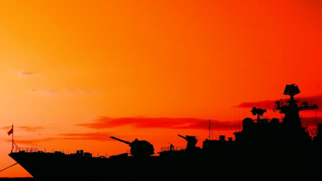 vidéos et rushes de silhouette d'un navire de guerre sur le fond de coucher du soleil - cuirassé