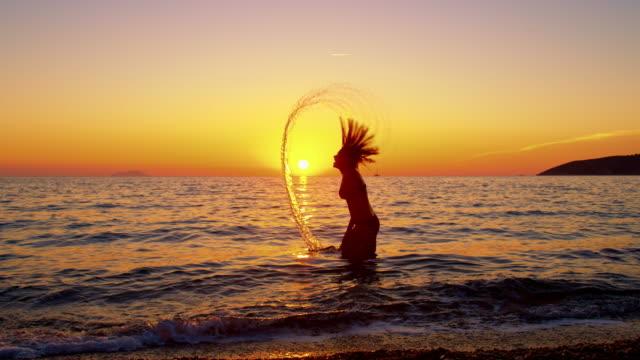 SLO MO silhouet van een vrouw die haar natte haren spiegelen