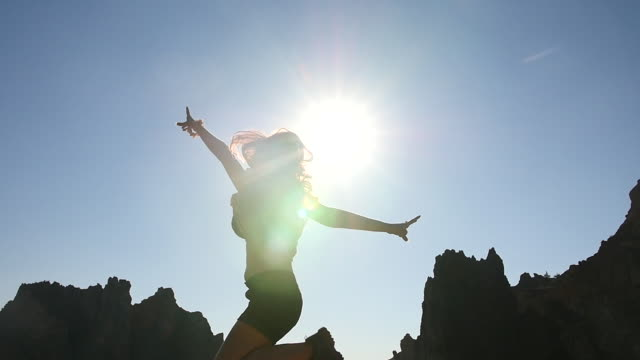 Silhouette of a Woman Jumping infront of the Sun, Slow Motion 2