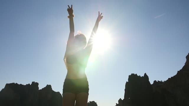 Silhouette of a Woman Jumping infront of the Sun, Slow Motion