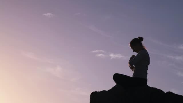 silhouette einer frau, meditieren am sonnenaufgang - meditieren stock-videos und b-roll-filmmaterial