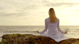 Silhouette of a woman meditating at the beach at sunrise
