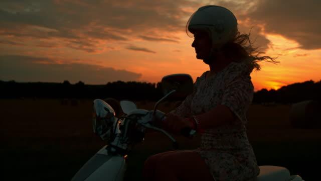 vídeos y material grabado en eventos de stock de time warp silueta de una mujer montando en scooter al atardecer - ciclomotor vehículo de motor