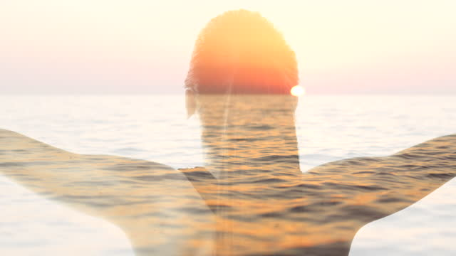 vídeos de stock, filmes e b-roll de ws silhueta de uma mulher de braços abertos contra um fundo do mar ao pôr do sol - equilíbrio
