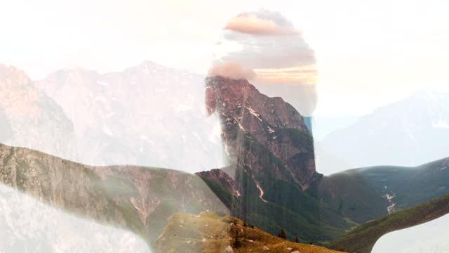 vídeos de stock, filmes e b-roll de ws silhueta de uma mulher de braços abertos contra um fundo de montanhas - mãos estendidas
