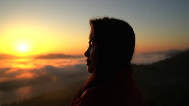 silhouette of a women hiker in the mountains with a sea of mist in the valley in the hours of sunset. - silhouette stock videos & royalty-free footage