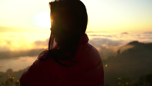 silhouette of a women hiker in the mountains with a sea of mist in the valley in the hours of sunset. - back lit stock videos & royalty-free footage