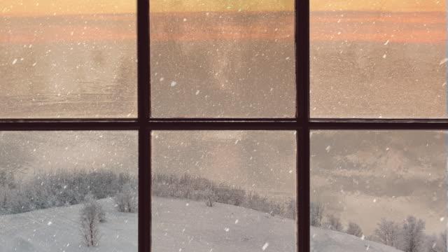 silhouette eines holzfensters mit blick auf den abendlichen winterwald. schöne winterlandschaft mit fallendem schnee - gemütlich stock-videos und b-roll-filmmaterial