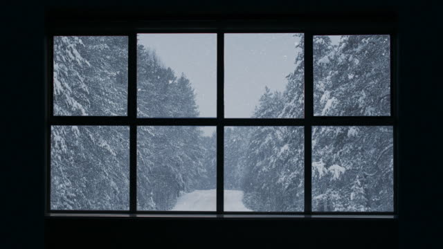 silhouette of a wooden window overlooking the winter forest. beautiful winter landscape with falling snow. - capanna di legno video stock e b–roll