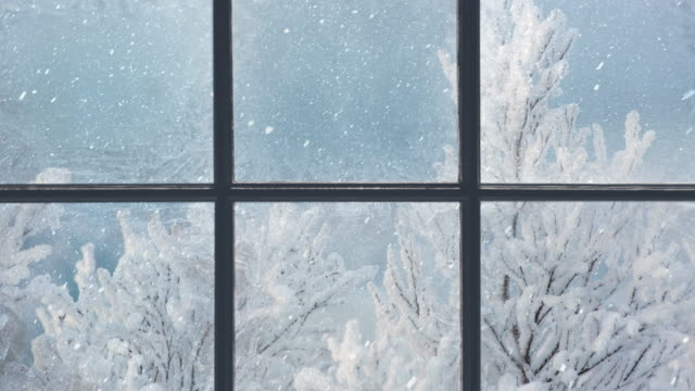 vídeos de stock e filmes b-roll de silhouette of a wooden window overlooking the winter forest. beautiful winter landscape with falling snow - aconchegante