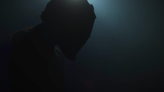 silhouette of a young female welder putting on her welding mask and welding with a mig torch - steel stock videos & royalty-free footage