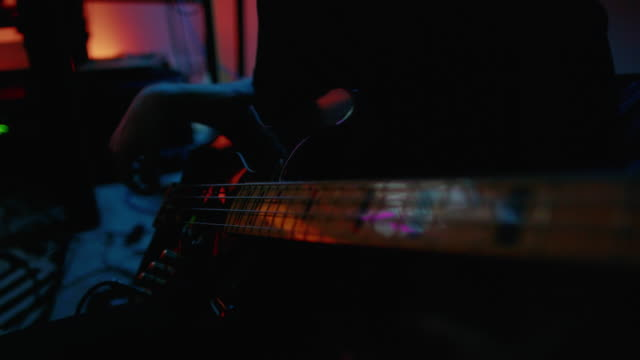 silhouette of a young man in his twenties playing the electric bass guitar in a dark room lit by multicolored lights in a recording studio - musician stock videos & royalty-free footage