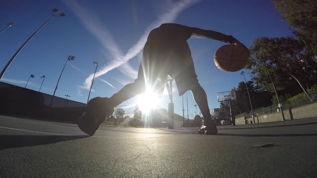 Silhouette of a young man playing basketball at a public park.
