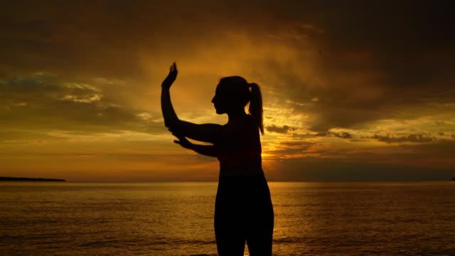 stockvideo's en b-roll-footage met silhouet van een jonge vrouw doet yoga tegen oranje hemel en zee tijdens zonsondergang - driekwartlengte