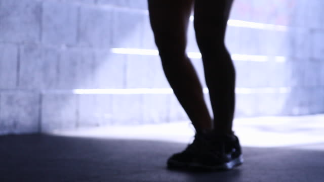 Silhouette of a young woman jump roping in a gym.
