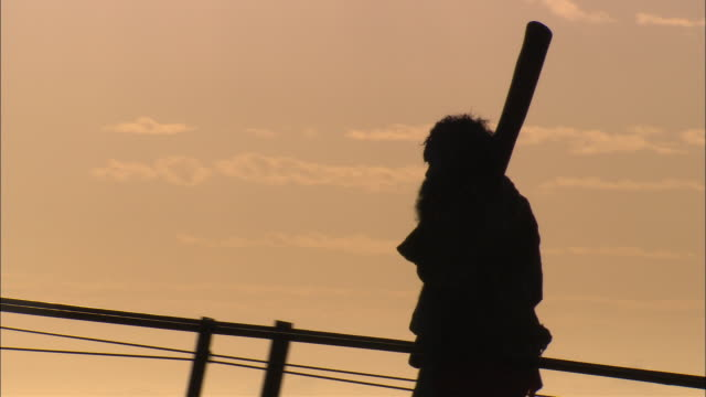 MS PAN Silhouette of Aboriginal man walking on Sydney Harbor Bridge with didgeridoo, Sydney, New South Wales, Australia