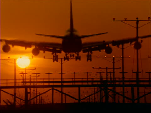 REAR VIEW silhouette of airliner (747) landing over signal lights at sunset / Los Angeles Airport