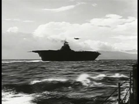 silhouette of allied carrier & single aircraft in flight above. signalman signaling w/ flag on flight deck. tracking f4f 'wildcat' fighter aircraft... - pacific war stock videos & royalty-free footage