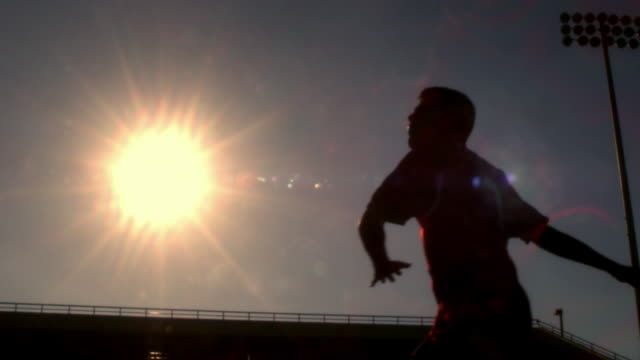 slo mo. silhouette of an athletic soccer player kicking a ball over his head in a stadium - athlete stock videos & royalty-free footage