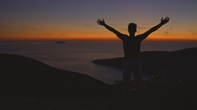slo mo silhouette of an ecstatic man raising his arms to the sky while enjoying the sunset over the sea - arms raised stock videos & royalty-free footage