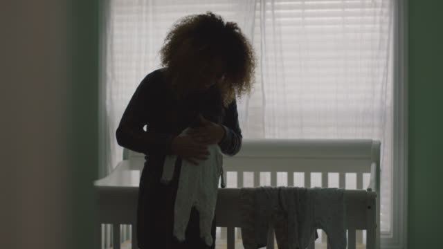 silhouette of an expecting multi-ethnic woman holding a onesie in baby's nursery - pregnant stock videos & royalty-free footage