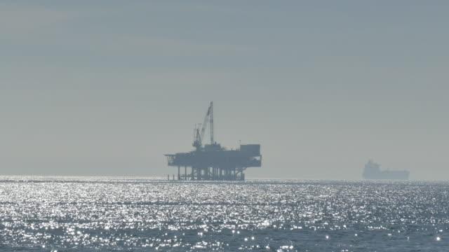 vidéos et rushes de silhouette of an offshore oil drilling platform and a oil tanker through the haze on the horizon - bras de mer mer