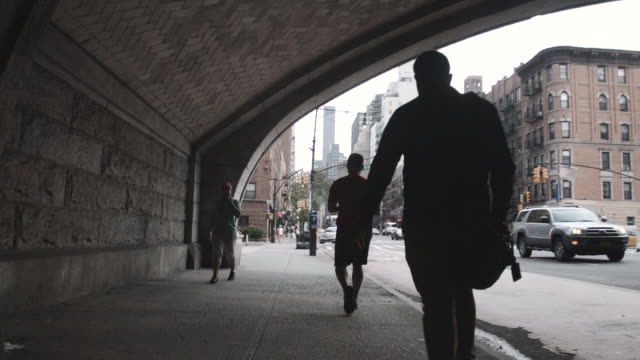 a silhouette of an unrecognizable man walking the streets of new york city. - en dag i livet bildbanksvideor och videomaterial från bakom kulisserna
