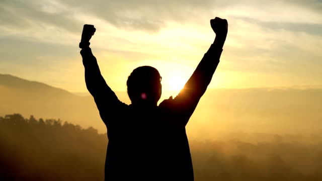 silhouette of arms raised man in sunrise - successo video stock e b–roll