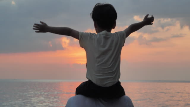 silhouette of asian baby boy ride the neck of father.dad and baby boy playing together outdoors on a summer at sunset.happy family watching the sunset on the beach.holiday travel concept.vacations - two generation family stock videos & royalty-free footage