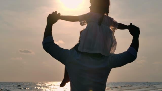 お父さんの首に乗るアジアの女の赤ちゃんのシルエット。日没の夏に屋外で一緒に遊んでお父さんと赤ちゃんの女の子。ビーチで夕日を見て幸せな家族.休日の旅のコンセプト。休暇-istock - おんぶ点の映像素材/bロール