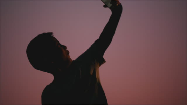 Silhouette of Asian boy is selfie while using smart phone