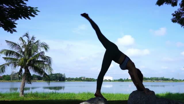 vídeos y material grabado en eventos de stock de silueta de cielo de yoga y pilates, atardecer y amanecer de entrenamiento mujer sexy asiática - flexionar los músculos
